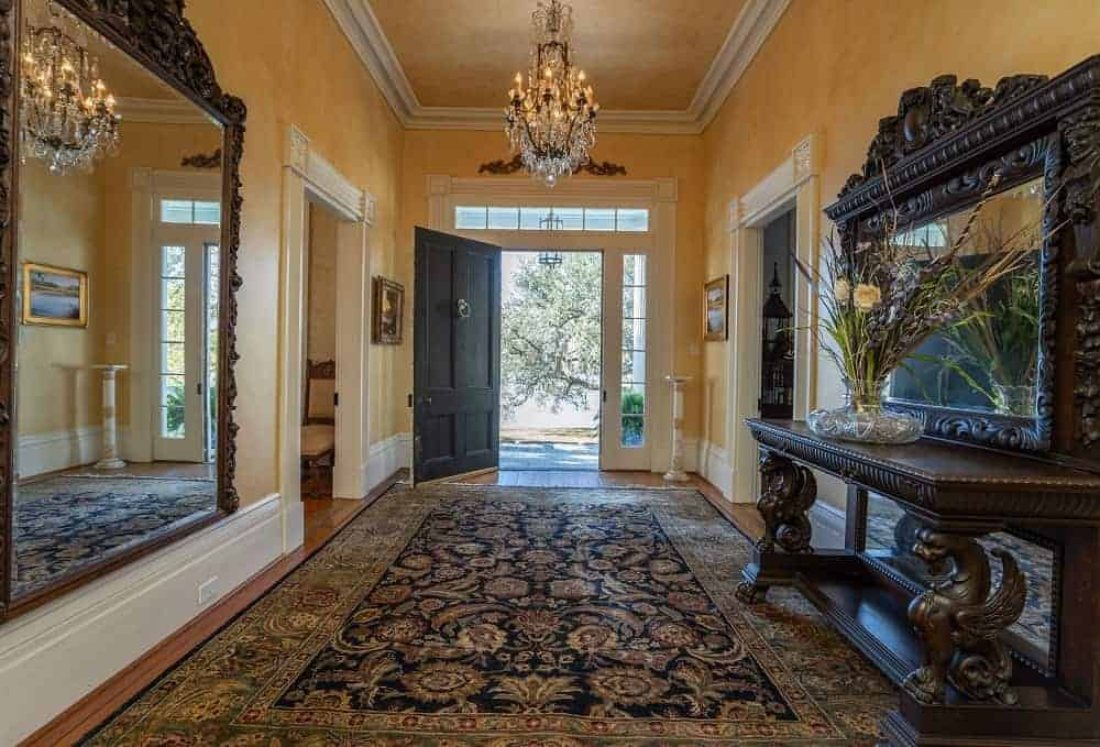 This foyer boasts a massive area rug and an elegant side table with a mirror. The hall is lighted by a gorgeous chandelier.