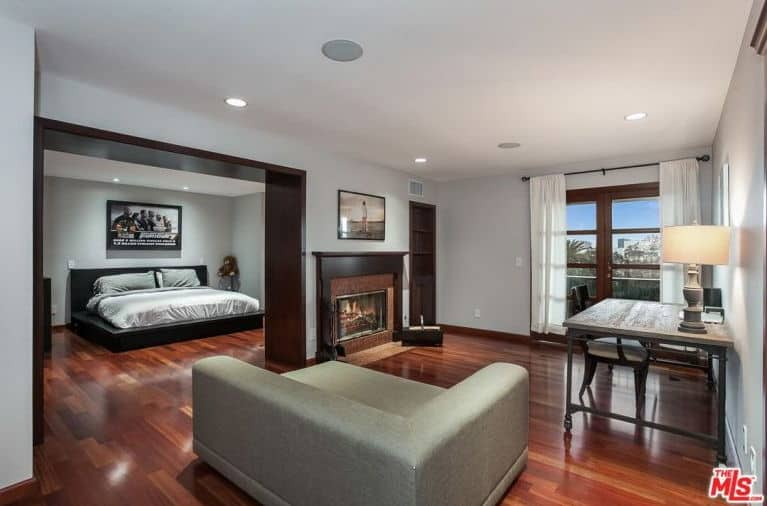 This large primary bedroom belongs to singer Charlie Puth. He includes a Fast and Furious wall decor on it, along with a large cozy bed, a fireplace, a table desk and a small modern gray couch.