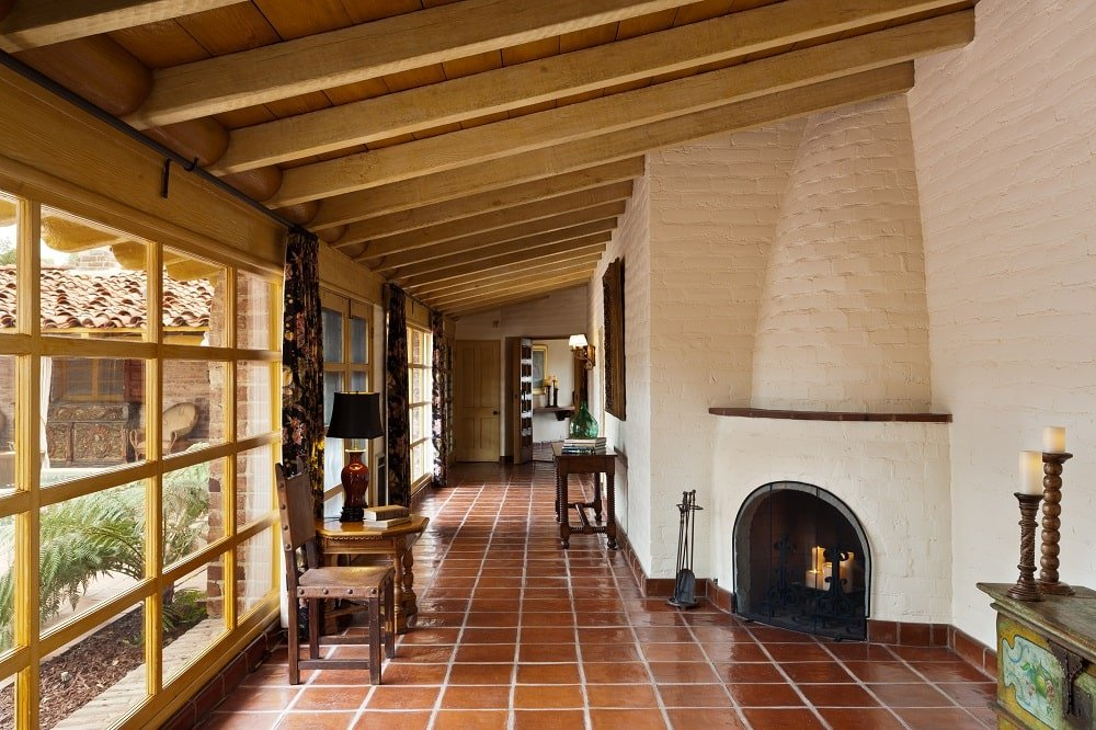 Upon entry of the house, you are welcomed by this foyer that has dark brown flooring tiles and a wooden shed ceiling with exposed beams. At the far corner is a small fireplace embedded onto the beige wall.