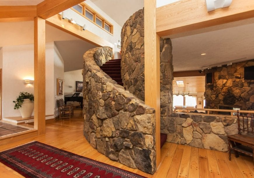 Upon entry of the house, you are welcomed by this foyer that has a spiral staircase with mosaic stone walls. These are then complemented by the hardwood flooring that matches with the wood beams and pillars.