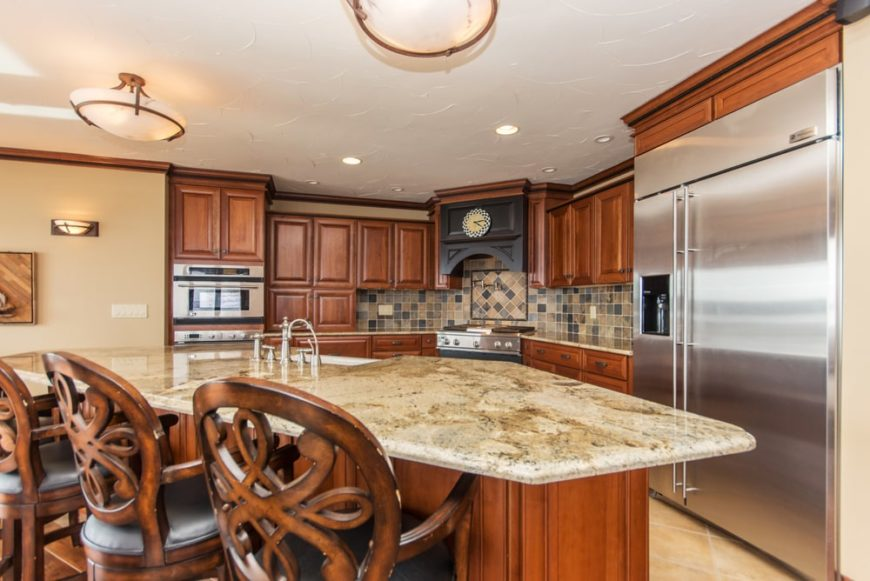 This is the kitchen with a large kitchen island. It has a beige marble countertop that contrasts the dark wooden cabinetry and stainless steel appliances.