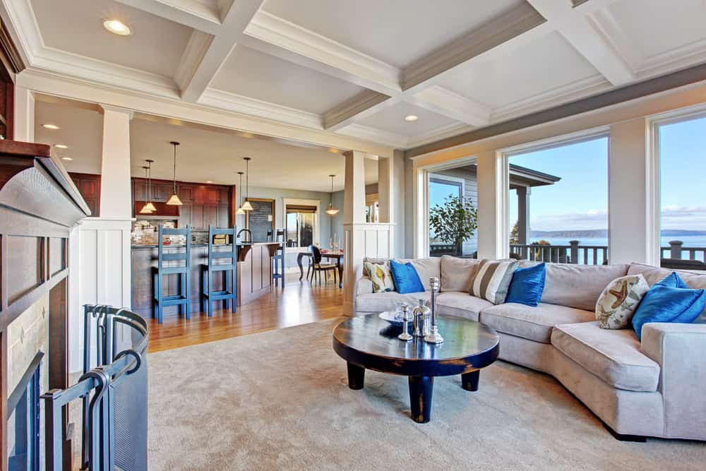 A distressed black coffee table stands out in this living area with coffered ceiling and picture windows framing a magnificent beach view. It is complemented by a gray sectional that's accented with blue and printed pillows.