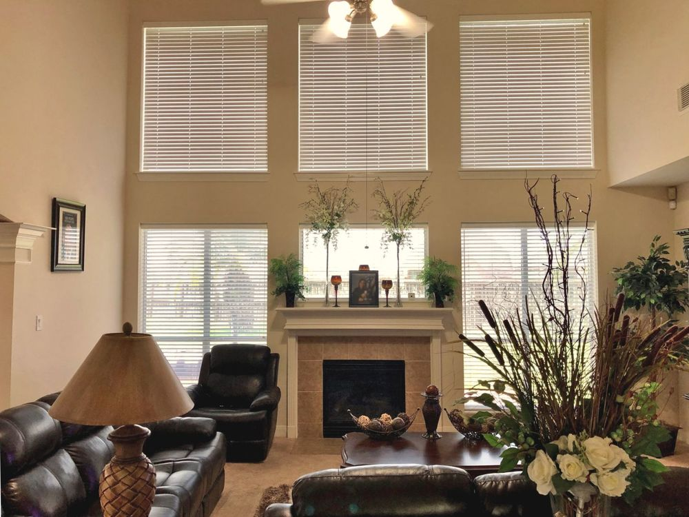 A formal living room boasting an elegant leather sofa set along with a fireplace set under the home's high ceiling. There are multiple windows as well featuring window blinds.