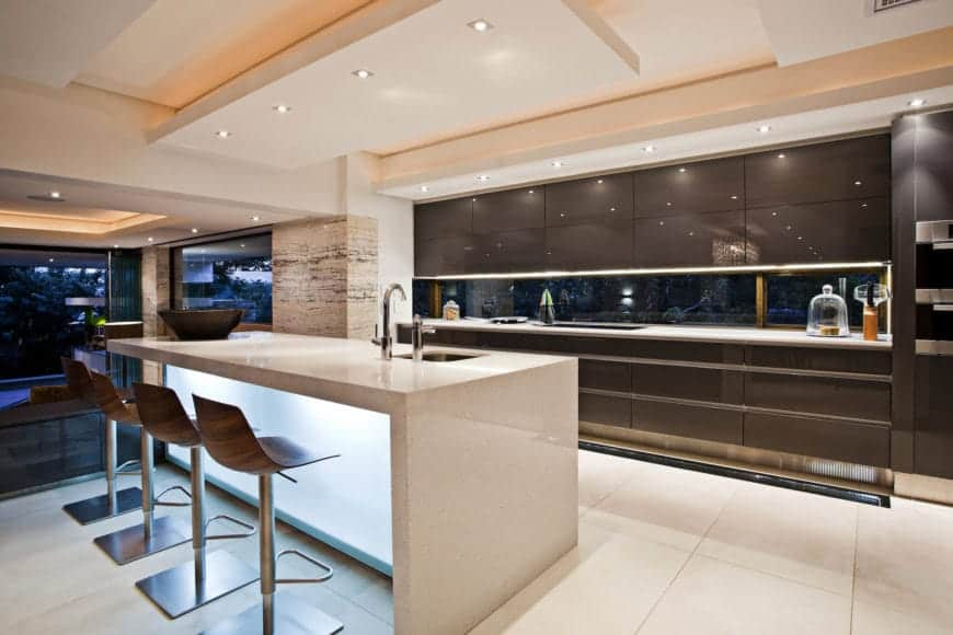 This is a brilliant and sleek Contemporary-style kitchen with a white waterfall kitchen island that blends with the white flooring and has a glowing frosted glass panel. This is paired with a chocolate brown kitchen peninsula lined with stainless steel details.