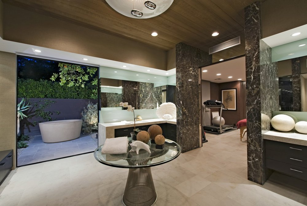 A contemporary master bathroom with tiles floors and a tall wooden ceiling. There's a glass top centerpiece table and a floating vanity sink counter. There's a powder desk area and a freestanding tub set outside.