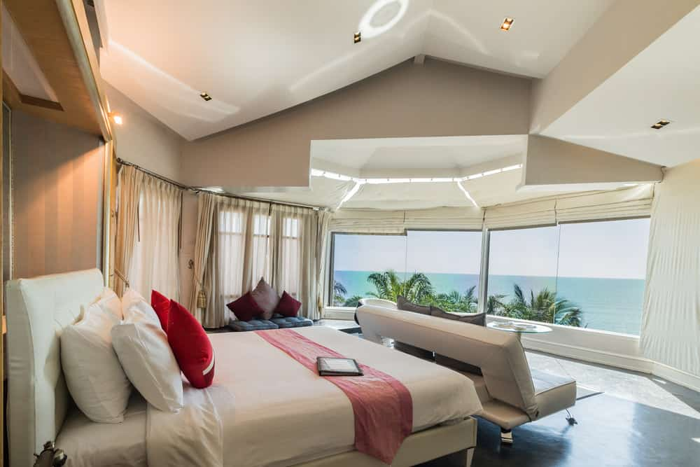 This primary bedroom features a comfy bed with a leather sofa on its end facing the panoramic window that overlooks a stunning beach view. It has cathedral ceiling and concrete flooring softened by flowy sheer curtains.