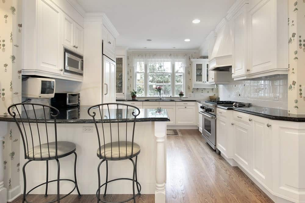 This is a Cottage-style kitchen that oozes with comfort and homey warmth with its hardwood flooring that balances the brightness of the white shaker cabinets and drawers of the small L-shaped peninsula with an attached breakfast island as well as the L-shaped structure lining the walls accented with minute details of the wallpaper.
