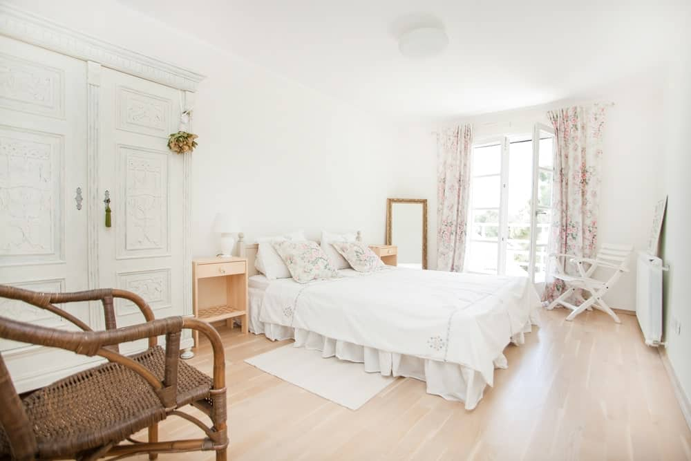Bright primary bedroom with light hardwood flooring and a French door covered in floral draperies. It boasts a skirted bed and a charming white wardrobe designed with intricate details.