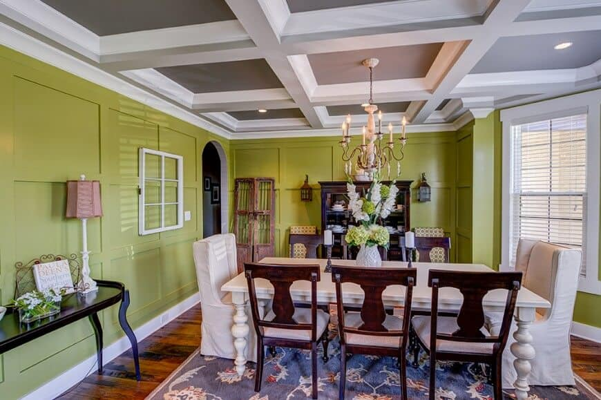 Green wainscoted walls surround this country-style dining room with hardwood flooring and a gray coffered ceiling mounted with recessed lights and a candle chandelier. It offers a cozy dining set with mismatched chairs sitting on a blue patterned rug.
