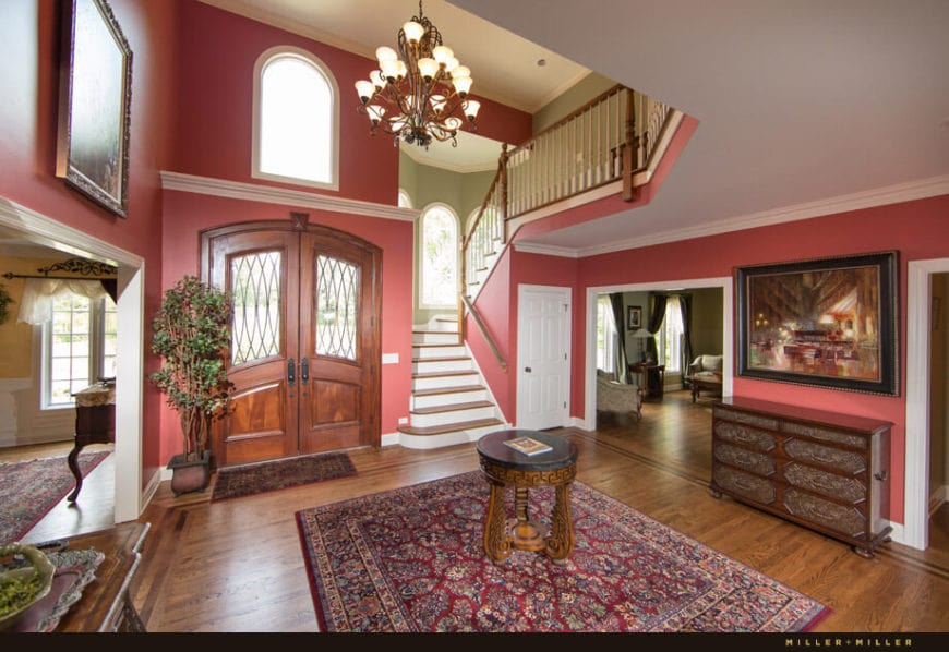 This gorgeous Country-style foyer has pink walls that match well with the red patterned area rug in the middle of the hardwood flooring. This matches well with the wooden double doors that have glass panels and adorned with a potted plant by the corner.