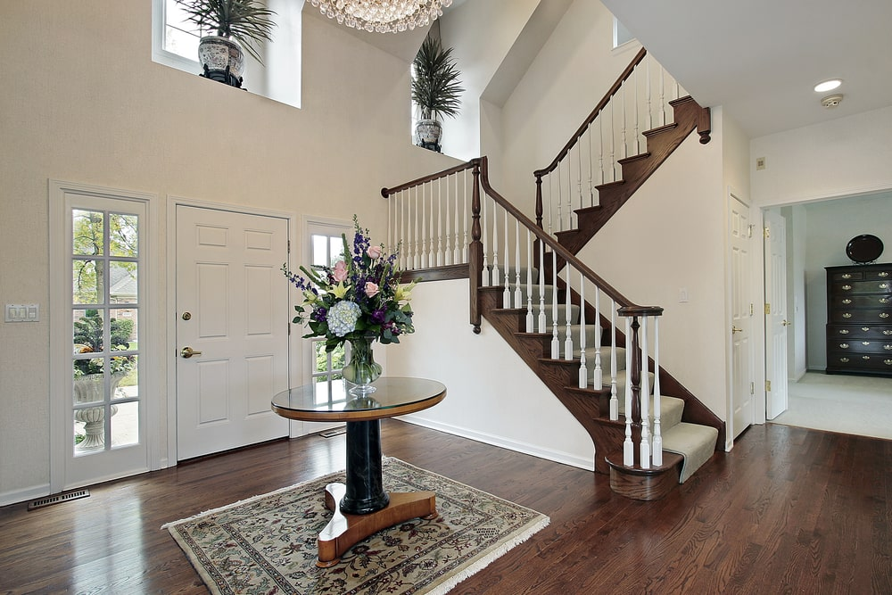 The white wooden main door of this Country-style foyer has brilliant side lights filled with glass panels. These bring in an abundance of natural lighting to the dark hardwood flooring that contrasts the bright beige walls that reaches to a high ceiling.