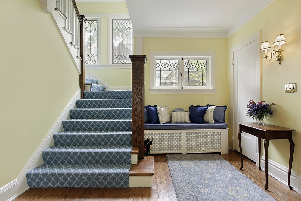 This is a small Country-style foyer that makes up for its small floor space with a comfortable welcome. It has a cushioned bench on the side by the wooden staircase that has light gray carpeted steps making it stand out against the cheerful yellow walls.