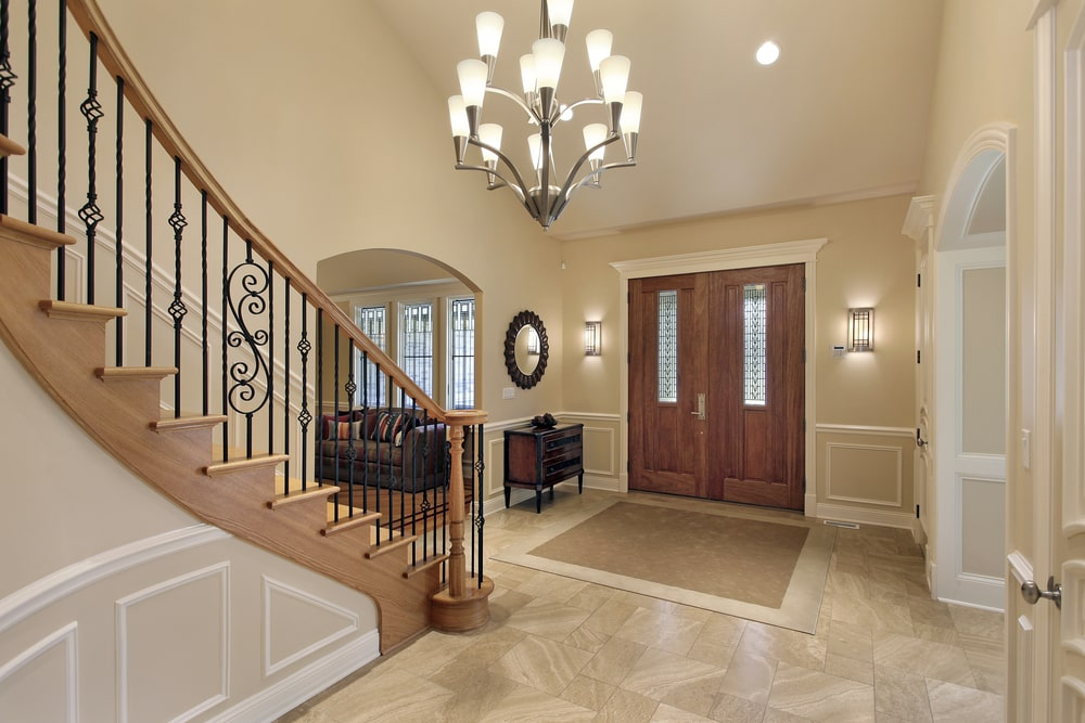 The beautiful chandelier of this foyer matches with the wall-mounted lamps flanking the main wooden door. All of these cast a complementing yellow light to the beige walls that matches well with the beige marble flooring that is topped with a simple area rug by the entrance.