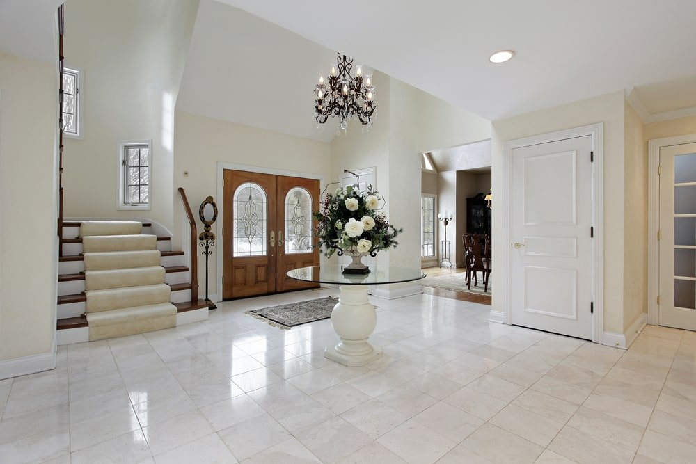 The intricate wrought iron chandelier that hangs from the high ceiling is the highlight of this elegant and spacious foyer. It also has a glass-top round table bearing flowers in the middle of the marble flooring that matches the brightness of the walls.