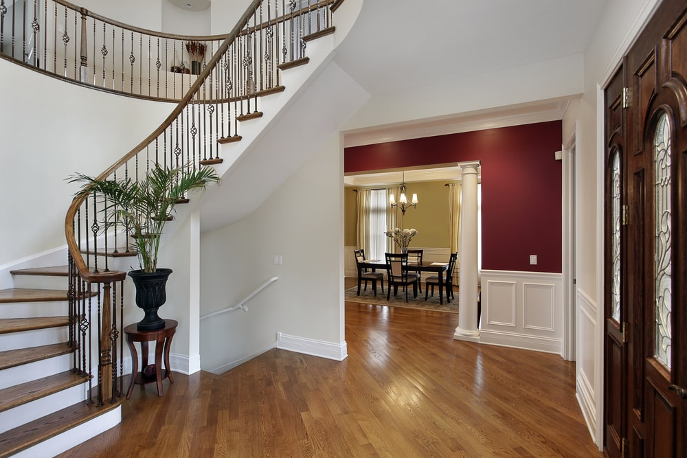 The white walls and white wainscoting of this Country-style foyer blends with the white ceiling. These are all contrasted by the wooden steps and banister of the staircase that pairs well with the hardwood flooring leading to the dining room that has an entryway flanked by white columns.