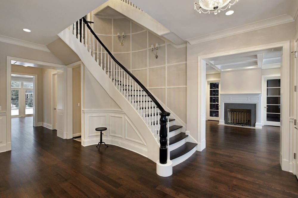 This is a simple and elegant Country-style foyer with the staircase as its highlight. This has a black wooden banister matching with the black wooden steps. These are then contrasted by the white wooden railings and the light hue of the walls.