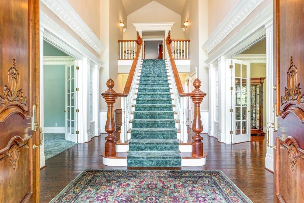 This Country-style foyer has wooden double doors accented with elegant carvings and golden door knobs. This matches well with the wooden banisters of the staircase that has a green velvet carpeting to pair with the green patterned area rug by the entrance.