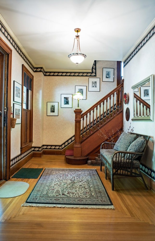 This is a charming Country-style foyer that has a lining pattern on its upper walls and lower walls just above the wooden molding. This matches with the wooden frames of the door and staircase railings and banister. This foyer has a cushioned dark bamboo bench for the waiting guests.