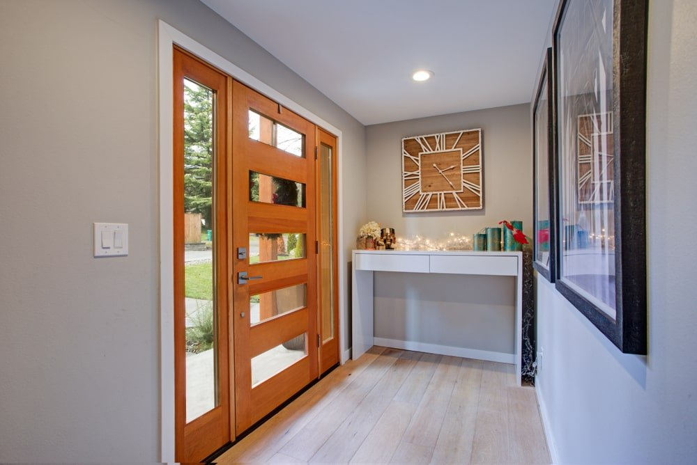This is a small Country-style foyer that is dominated by its large wooden main door. This has a unique design that is dominated by narrow glass panels. This makes it stand out against the light gray walls, ceiling and the light hardwood flooring as well as the console table underneath the decorative clock.