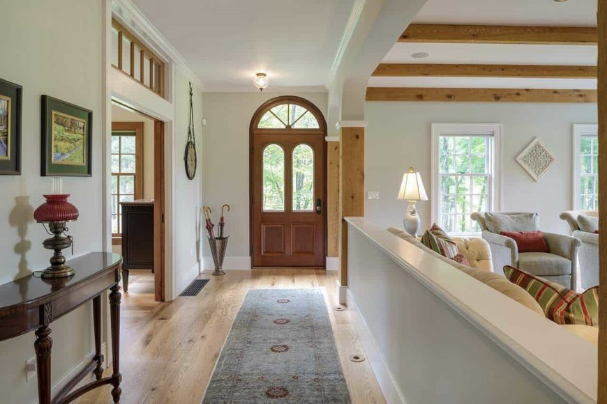 This is a simple and narrow Country-style foyer. It has a hardwood flooring that is topped with a narrow gray area rug that complements the light gray walls. The light hue of these wall make the wooden console table and the umbrella rack by the main door stand out.
