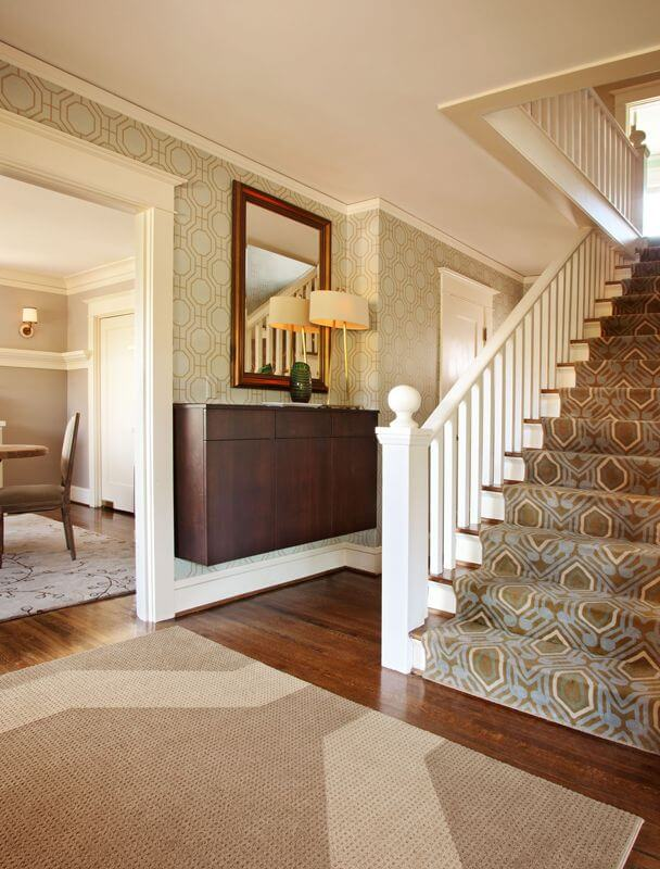 The charming patterned wallpaper of this Country-style foyer matches well with the patterns of the green and blue carpeting of the stairs. This contrasts the stark white wooden railings of the staircase. Next to this is the floating cabinet that also acts as a console table bearing a lamp.