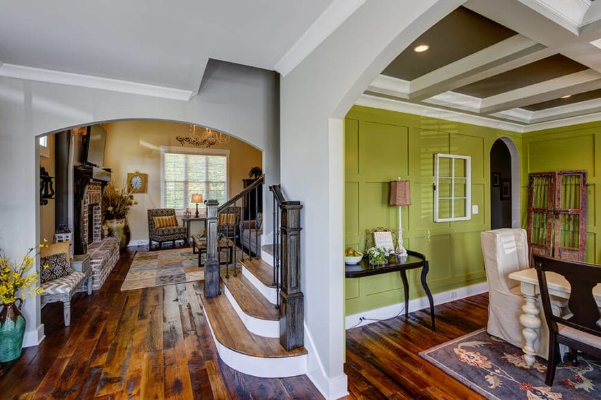 This view from the foyer of this Country-style home shows the dining room on the right through an arched walkway. Then directly in front is the bottom of the stairs that has wooden steps to match the hardwood flooring leading to the arched entryway of the living room area.
