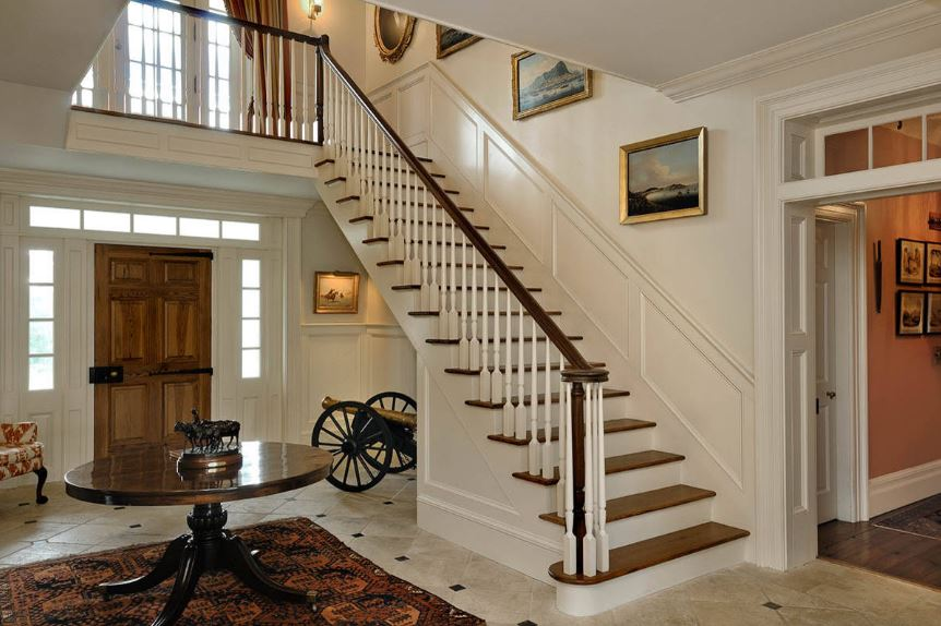 This eclectic Country-style foyer has a war theme to it with the decoration of the vintage cannon made of gold and black wood on the side standing out against the white wainscoting and white walls. This is augmented by the round wooden table by the wooden stairs.