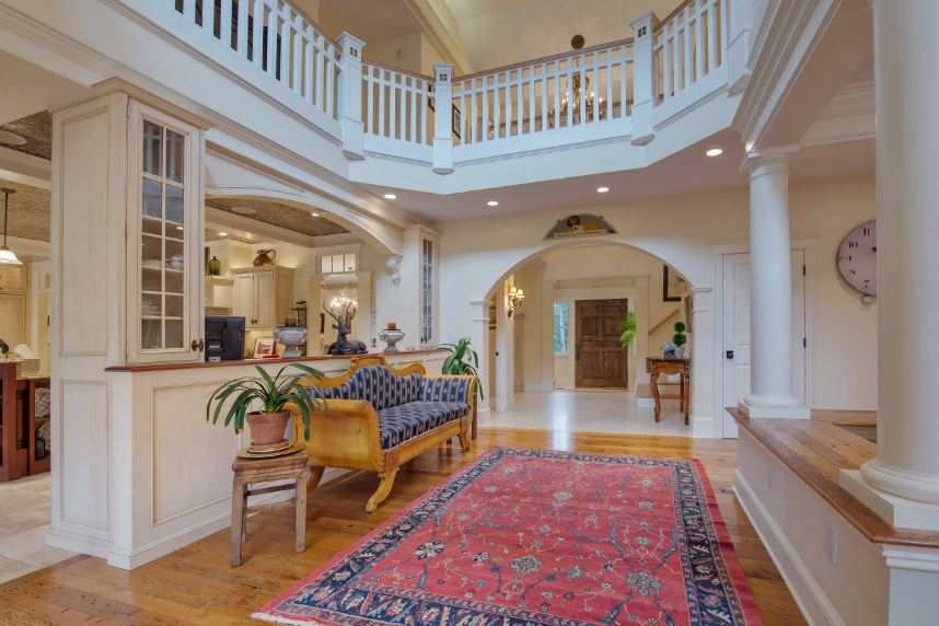 This is a charming Country-style foyer with a tall ceiling giving a clear view of the second floor wooden railings. This matches with the white wooden walls and the white pillars on the side. A dash of color accents this room from the area rug and the potted plants flanking the wooden bench.