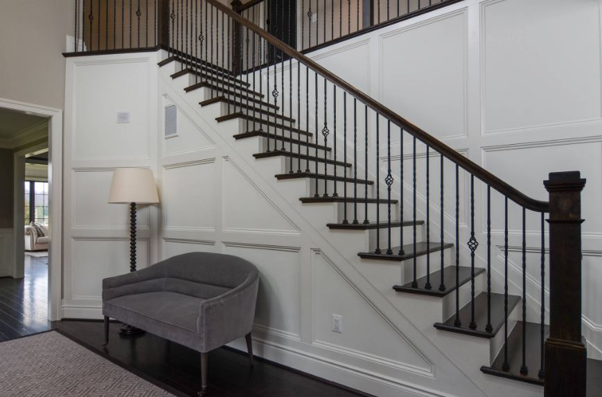 The elegant finish of the white wooden walls of this Country-style foyer is complemented by the gray cushioned bench beside the standing lamp. The white tones are contrasted by the black hardwood flooring and the pitch black banister and wrought iron railings of the stairs.