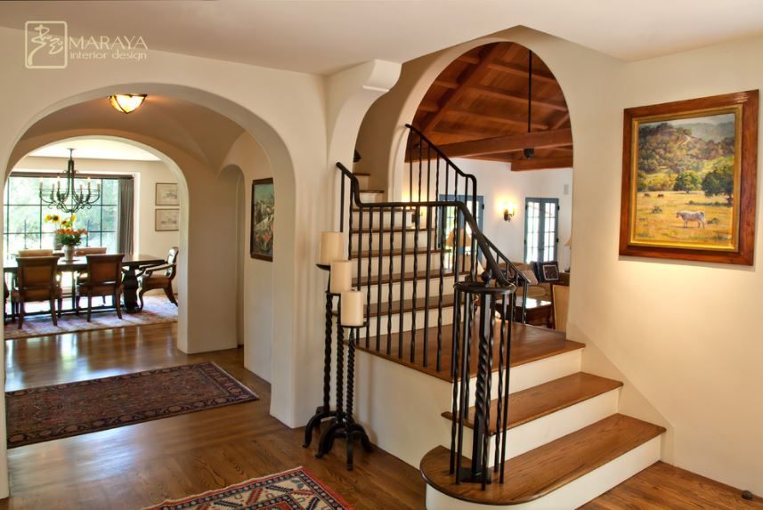 This is a small Country-style foyer that has beige walls and ceiling adorned with with a colorful painting of a horse in a meadow. These light tones also make the wrought iron railings and candelabras stand out complemented by the hardwood flooring.