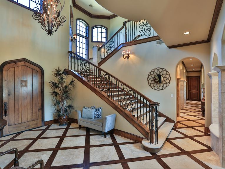 The wooden main door has a charming arched design that fits well with the diamond patterns of the flooring that seems to be a combination of wood and marble. This Country-style foyer is adorned with a potted plant at the corner beside the cushioned gray bench.