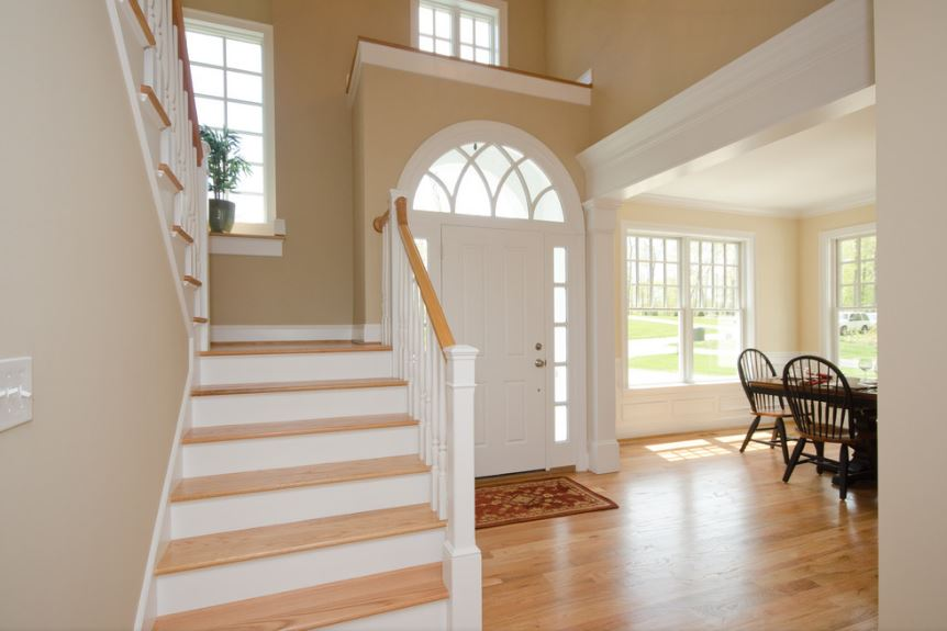 The arched transom window of the white main door stands out against the earthy beige tones of the walls. This also brings a brightness for the light hardwood flooring that is adorned with a small colorful patterned area rug by the entrance to serve as a welcome mat.