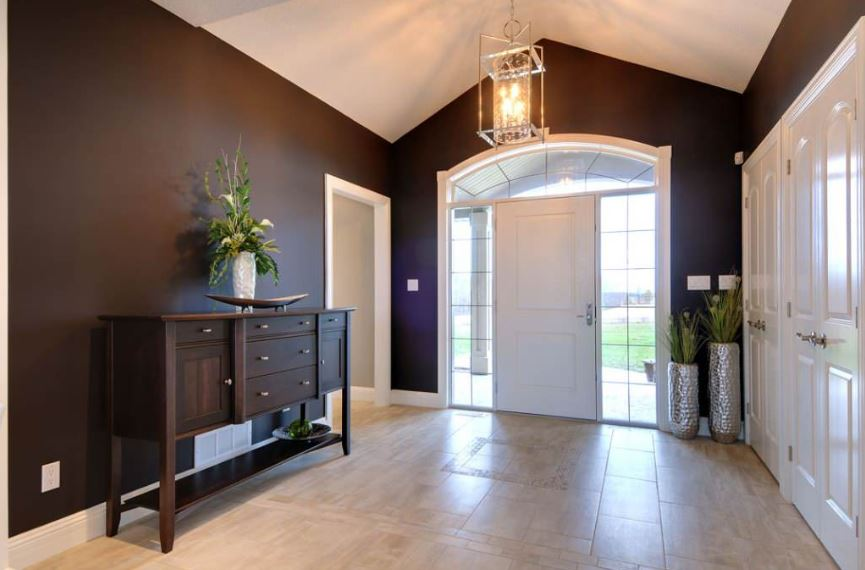 The black walls of this Country-style foyer is complemented by the dark wooden console table that bears a bouquet of flowers in an elegant vase matching the tall and thin pots by the brilliant side lights of the white main door brightened by a large lantern pendant light from the cathedral ceiling.