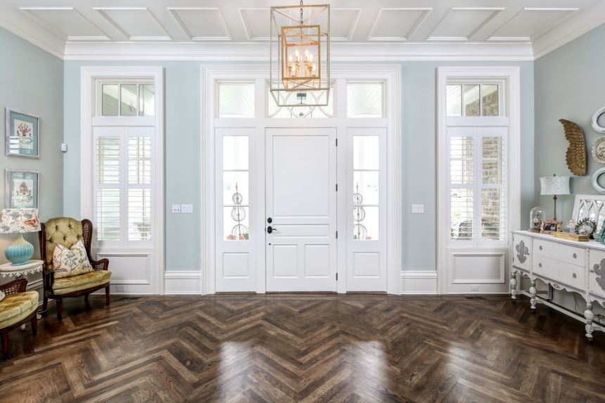 The hardwood flooring of this spacious foyer has a herring bone pattern that gives a degree of complexity to the simple light blue walls and the white elements of the main door, windows and the white ceiling that has its own patterns to match the decorative pendant light.