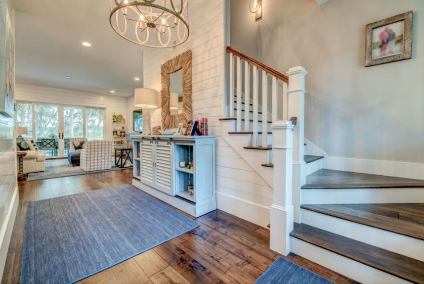 This is a homey Country-style foyer with a hardwood flooring covered with a couple of gray area rugs matching with the light gray walls and the light gray waist-high cabinet by the stairs that also function as a console table topped with a wall-mounted mirror and a lamp.