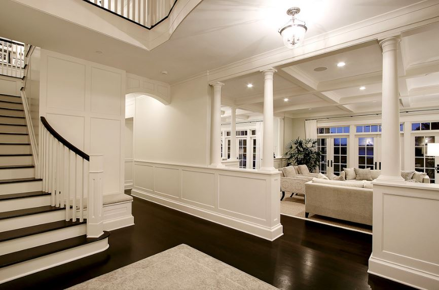 This simple foyer has white walls, white wainscoting and a bright white ceiling complemented by the white lights of the small glass pendant light. This is also matched with the light hue of the area rug and the small white pillars flanking the entryway to the living room.