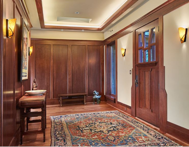 This is a simple foyer with matching tones on the main wooden door, its frame, the wooden walls, the lining of the cove ceiling and the wooden console table that blends with the wooden walls. This is mirrored by the small wooden bench on the adjacent side.