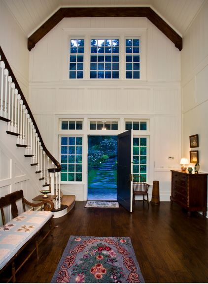 This amazing and breathtaking Country-style foyer has a high white cove ceiling outlined with exposed wooden beams on the corner right above the large transom windows that pair well with the design of the small windows framing the wooden main door.