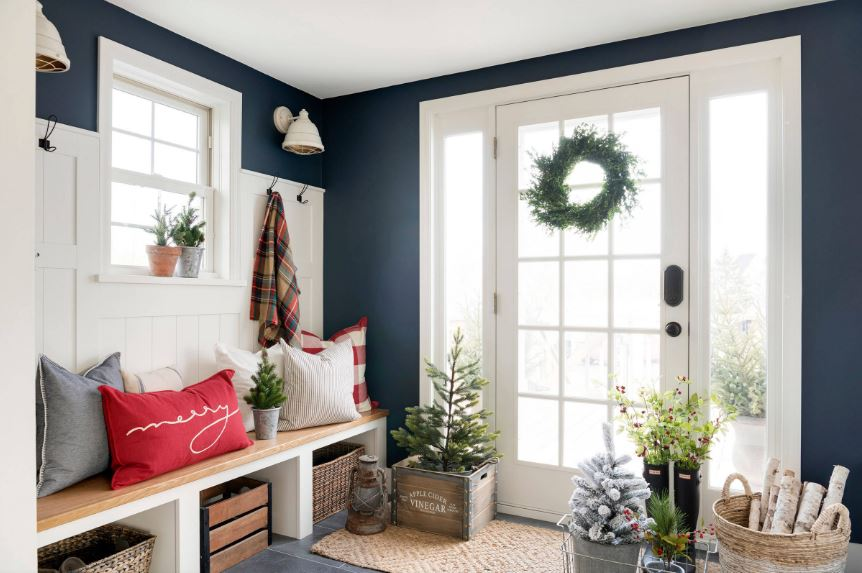 This charming Country-style foyer is in full Christmas mode with its rustic decorations that give an extra warm welcome to those entering through the white main door dominated by multiple glass panels. This brings in an abundance of natural lights to brighten the white wooden mudroom on the left.