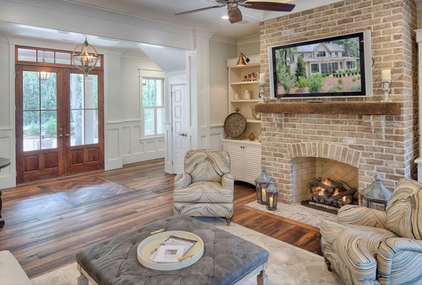 The small Country-style foyer is right beside the living room of this home that is warmed by the stone brick fireplace with a mounted TV above. The foyer is adorned with a spherical decorative pendant light that stands out against the white walls and the white ceiling.
