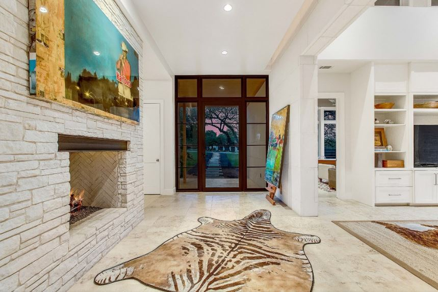 This unique Country-style foyer has a consistent light hue on its white walls, white ceiling and light marble flooring as well as the white stone housing of the fireplace. These are adorned with colorful artworks and vintage posters as well as a zebra print area rug.