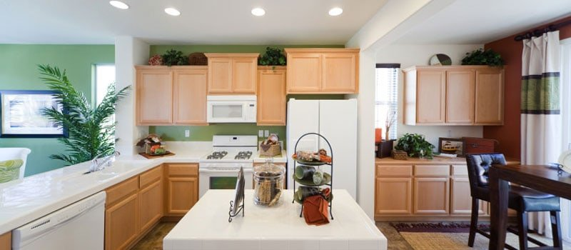 This is a delightful and cheerful Country-style kitchen with its bright green walls that complement the bare wooden tone of the L-shaped peninsula. This is paired with a small square kitchen island that has a white countertop to match the white ceiling.
