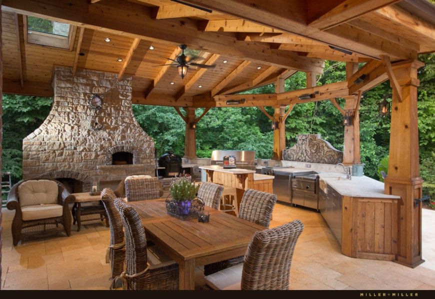 This is the outdoor kitchen and dining area of this home that has a charming wooden cathedral ceiling with exposed wooden beams complemented by the textured stone pillar of the fireplace. The open side of this area features the lush greenery of the Country-style landscaping surrounding the area.