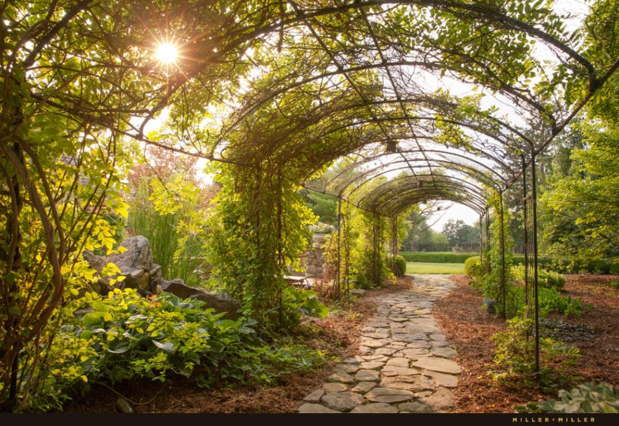 This is a charming path that leads to the grass lawn of the backyard. It has a rough mosaic stone walkway that goes through an arched corridor covered by creeping plants top provide some shade for those passing through the charming path.