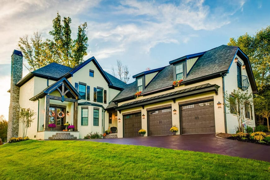 The Country-style landscaping of this home aims to highlight the natural beauty of the home instead of veer attention from it. The earthy driveway and walkway leads to three brown garage doors that are adorned with bright flowers matching those on the main entryway.