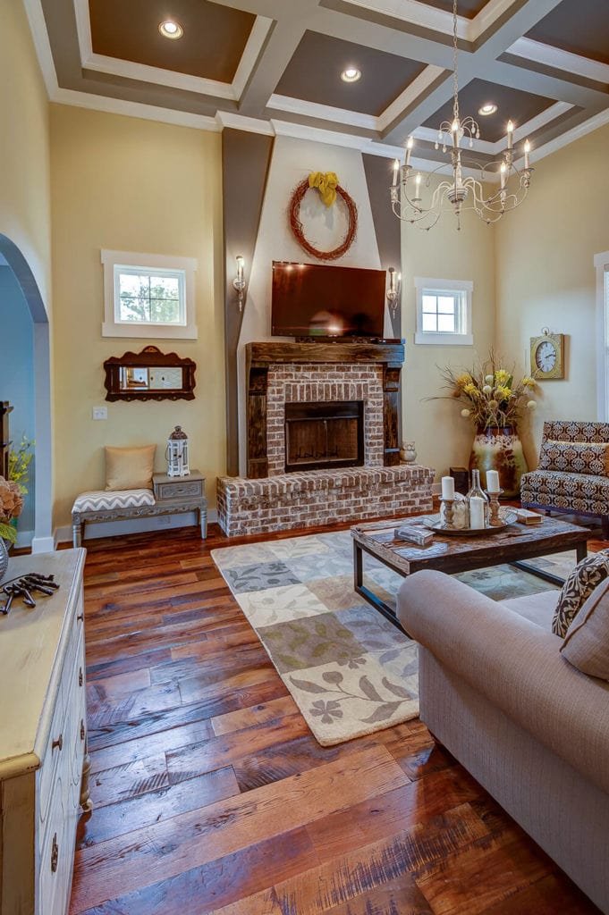This is a country-style living room with an elegant gray coffered ceiling hanging a thin chandelier over the rustic wooden coffee table near the fireplace that is housed with red bricks and a wooden mantle that supports the wall-mounted TV.