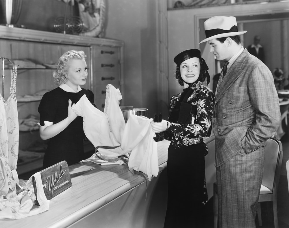 A couple speaking with a clerk.