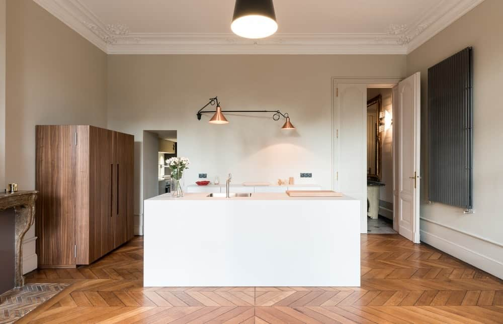This large kitchen has a wide white cove ceiling that matches with the white walls and white kitchen island. This makes it stand out against the hardwood flooring that has a pattern to it giving a certain complexity to the aesthetic of the kitchen.