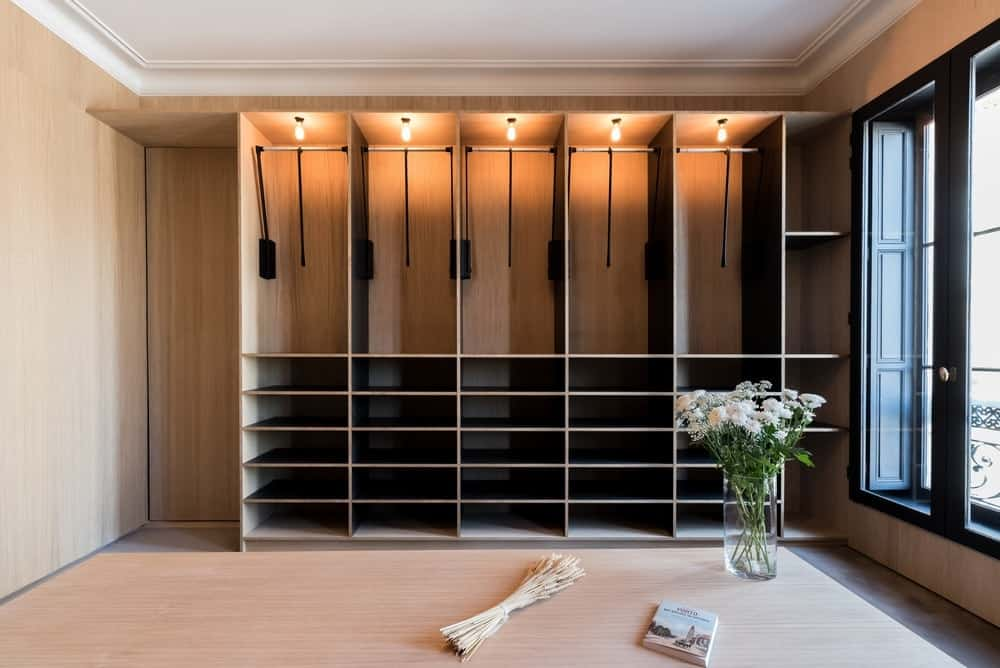 The bare wooden walls of this walk-in closet matches with the wooden structures of shelves for storage. This is illuminated by the tall glass window on the side with a contrasting dark frame making it stand out against the white cove ceiling.