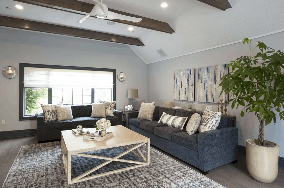 The exposed dark brown wooden beams stand out against the white shiplap cove ceiling that complements the light gray walls. These walls are accented with the couple of colorful abstract paintings, table lamp and a potted plant beside the charcoal gray sofa.